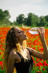 woman in field of poppy seed drink water from bottle