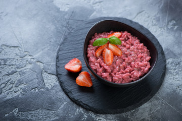 Black bowl with strawberry risotto on a stone slate tray, studio shot over grey stone background