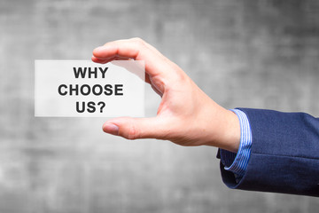 Businessman hand holding Why Choose Us? sign isolated on grey background. Business concept. Stock Photo