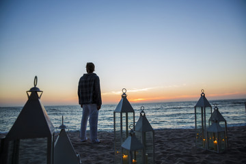 Man looking at sunset on a candle filled resort beach