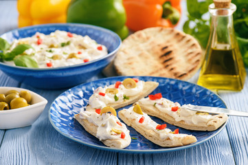 Feta cheese spread with olives and pepper served with pita bread. Greek style dish.