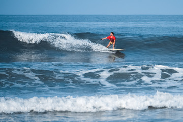 Amateur surfer rides the wave in the ocean