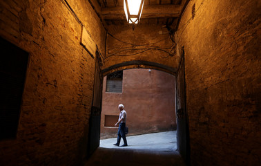 An elderly man walks in the old city centre of Siena