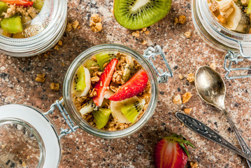 Healthy breakfast. Diet. Overnight oatmeal in a can, muesli. Yogurt with homemade granola and organic fruits - kiwi, banana, strawberry. On the stone table. With ingredients and spoons.