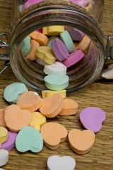 candy hearts spilling out of glass jar