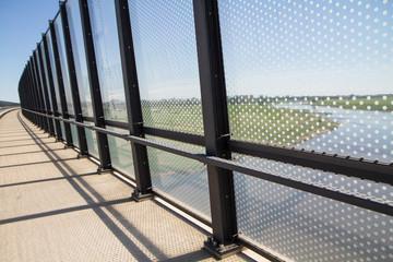 Windschutzwand aus Glas auf einer Brücke über der Elbe