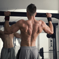 Bodybuilder pulls up in the gym, muscular man performing exercises on the horizontal bar