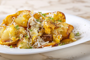 Fried potatoes with scrambled eggs and parmesan cheese on plate