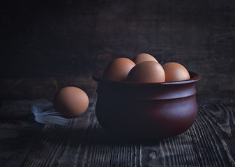 Chicken eggs in a clay bowl on a dark rustic table. Low key.
