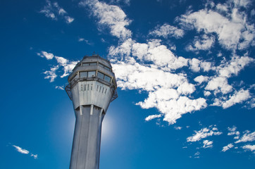 Airport traffic control tower with background of the sky and clouds.