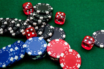 Poker chips and dice on a green gaming table top view copyspace close up