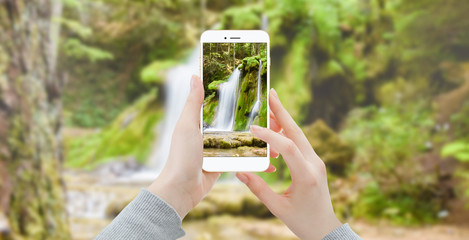 Girl taking photo of waterfall in the woods with modern smartphone