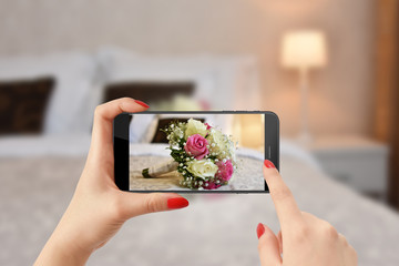 Girl taking photo of wedding bouquet with modern phone
