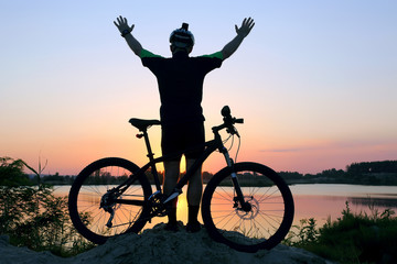 silhouette of a standing cyclist with arms raised with a bike at sunset.