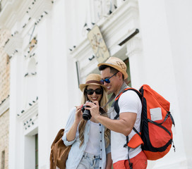 Beautiful young tourist couple looking at pictures