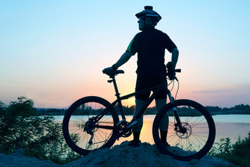 silhouette of a standing cyclist with bike at sunset.