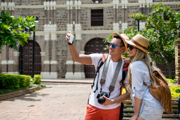 Pretty couple doing tourism taking a selfie with a smartphone