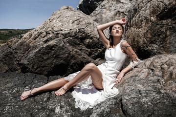 gorgeous beautiful boho girl sitting on huge stone