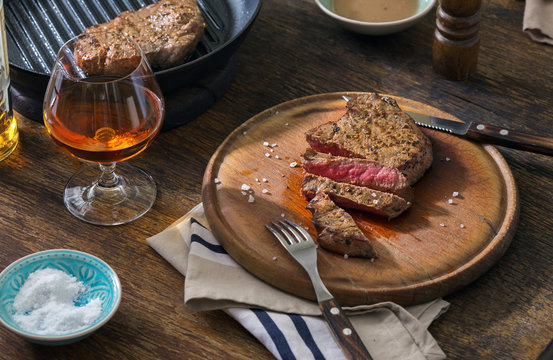 Beef rare grilled steak on wooden board with whiskey