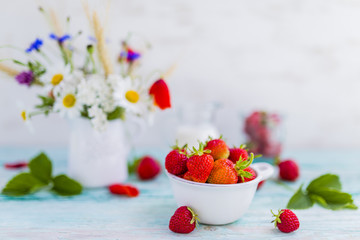 Fresh strawberries and wildflowers in a jug on wooden table.