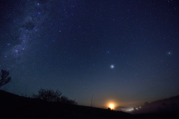The moon setting with part of the milky way on the left