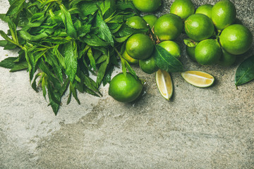 Flatlay of freshly picked organic limes and mint for making cocktail or lemonade over grey concrete stone background, top view, copy space