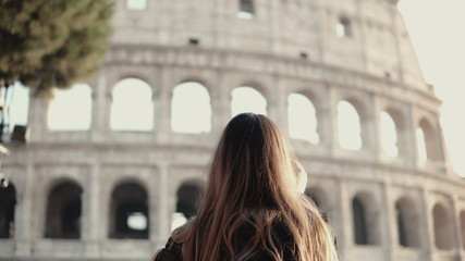 Young brunette tourist exploring the Colosseum in Rome, Italy. Woman takes the photo of sight, uses smartphone.