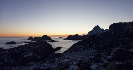 Sunset behind cliffs in the sea in Lofoten Norway