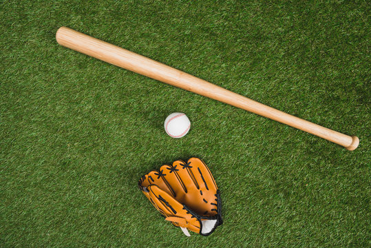 Top view of baseball bat with glove and ball on green grass