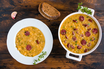 Hearty and healthy split pea and smoked sausage soup with green thyme in a white plate and casserole on the wooden table, top view.