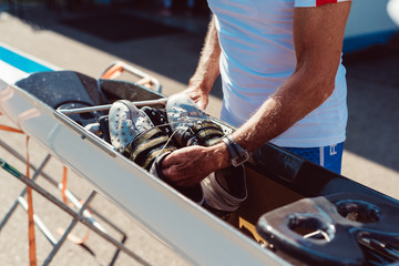 Midsection of man placing shoes in racing shell foot stretcher