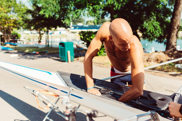 Rower preparing racing shell outdoors