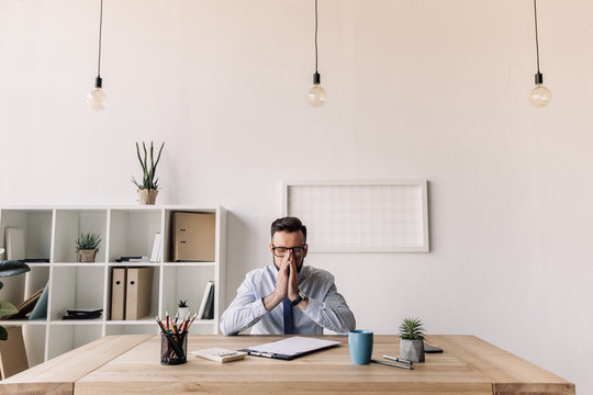 thoughtful bearded businessman sitting at table in modern office
