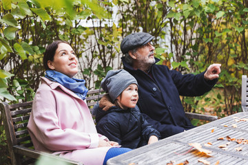 Senior man gesturing while sitting with great grandson and daughter at wooden table in park