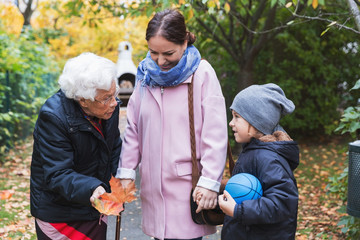 Senior woman holding autumn leaf while talking to great grandson and daughter in park