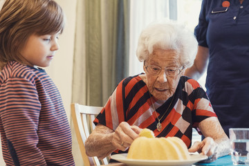 Boy and great grandmother looking at sponge cake in house