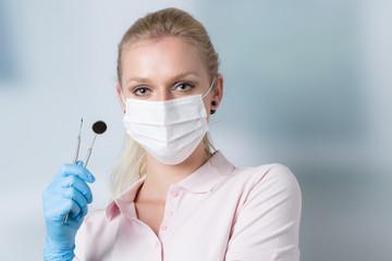 hübsche Zahnärztin mit Zahninstrumenten und Mundschutz