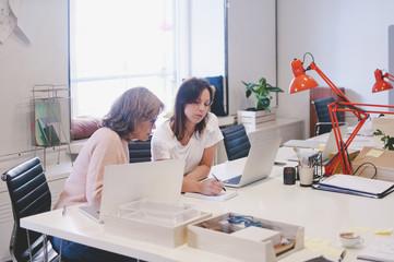 Businesswomen working at desk in creative office
