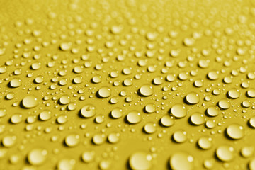 Water drops on smooth surface, yellow background