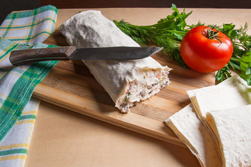 Pita bread or lavash wrapped with cottage cheese or curd, chicken, tomatoes and herbs - dill, onion, parsley. Lavash roll with vintage knife on cutting board.