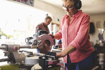 Senior woman using circular saw while man standing in background at workshop