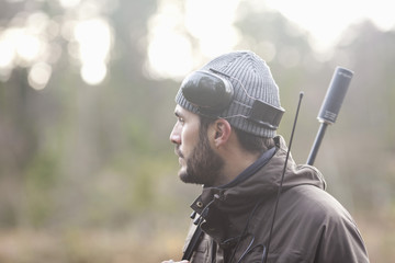 Side view of thoughtful male hunter in forest