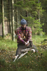 Mid adult man cutting firewood with axe in forest