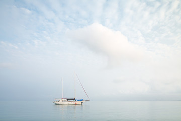 Sailing boat anchored in the middle of a calm sea