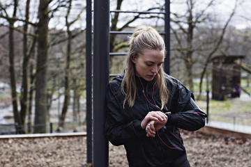 Female athlete checking smart watch while leaning on monkey bars in forest