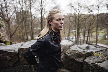 Side view of thoughtful female athlete standing by rocks in forest