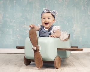 fröhliches Baby spielt mit Holzflieger