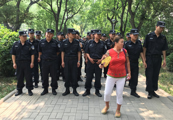 A woman stands in front of a police cordon near a protest in Beijing