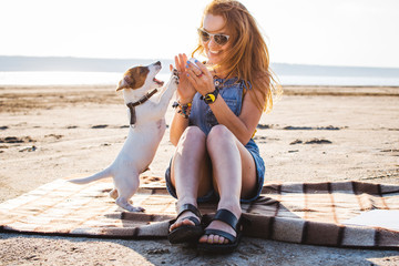 Young stylish hipster girl playing dog puppy jack russell on the beach