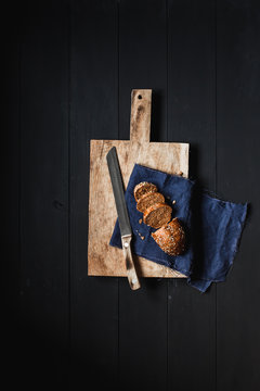 .Sliced bread and knife on a chopping board on a black wooden table